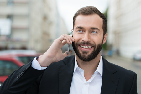 Attractive bearded businessman smiling as he takes a call on his mobile phone while standing outdoors in an urban setting photo