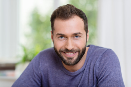 Hlava a ramena portrét usmívající se vousatého muže při pohledu na fotoaparát s přátelským úsměvem, v interiéru doma