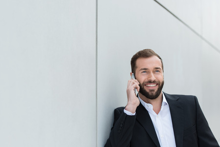 chats: Businessman smiling as he chats on his mobile looking up into the air with a smile of delight as he listens to the conversation Stock Photo