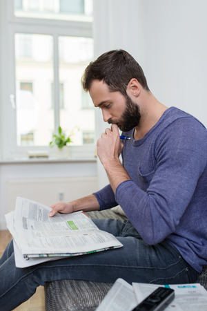 concentrates: Thoughtful man sitting reading a newspaper at home with his hand to his chin as he concentrates on the news