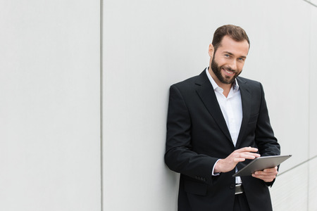 businessman smiling: Successful businessman standing using a tablet to access the internet as he leans against a white wall with copyspace