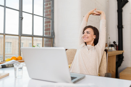 Happy relaxed young woman sitting in her kitchen with a\ laptop in front of her stretching her arms above her head and\ looking out of the window with a smile