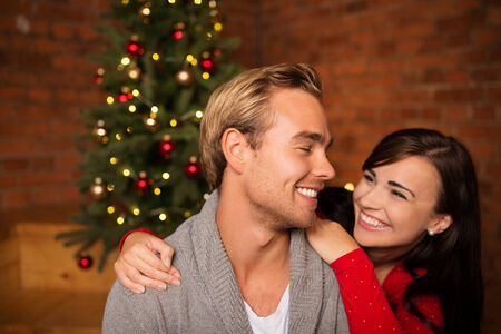 winter couple: Attractive happy couple on Christmas day standing in front of the decorated tree smiling lovingly into each others eyes