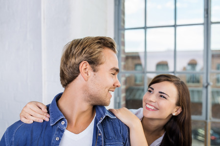 caresses: Playful loving couple standing in front of a large glass window smiling into each others eyes as the woman caresses her husbands shoulders Stock Photo