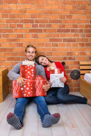 Smiling Sweet Young Couple Sitting on Floor Holding Christmas Gift Boxes. Leaning on Bricks Wall Background. photo