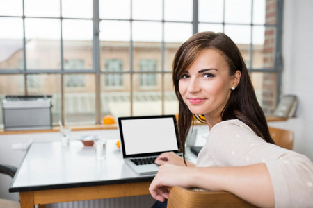 turning table: Attractive young woman with a cute smile turning in her chair to smile at the camera while sitting at a table with a laptop computer