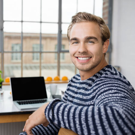 one young man: Portrait of an attractive young man sitting at a table working on a laptop turning in his chair to smile at the camera