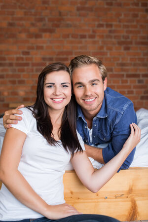 domiciles: Sweet Young White Couple Looking at Camera. Girlfriend Sitting on Floor While Boyfriend Lying on the Bed. Stock Photo