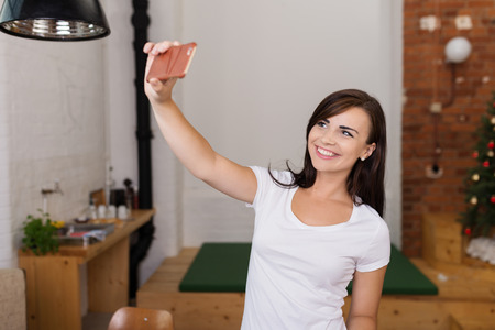 Attractive Smiling Young Female in White Shirt Taking Self Picture Inside the House. photo