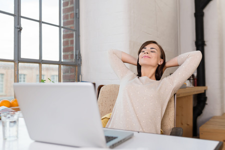 Young woman relaxing in her kitchen leaning back in a chair with her hands clasped behind her neck and her eyes closed in front of a laptop Reklamní fotografie