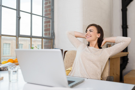 woman from behind: Happy woman relaxing in her kitchen with her laptop on the counter looking out of a window with a lovely smile
