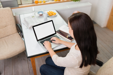 home computer: High angle view of a young woman working on a laptop computer at home in the kitchen, view of the blank screen Stock Photo