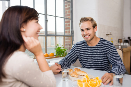 clinker: Affectionate couple enjoying a fresh breakfast together of oranges and croissants holding hands and laughing