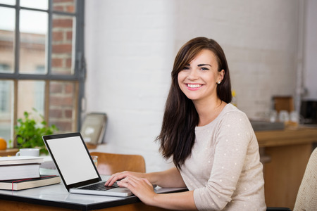 Gorgeous woman with a happy beaming smile sitting at a table working at a laptop computer in front of a window Stock Photo