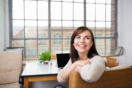 Happy relaxed young woman with a lovely smile turning to look over the back of her chair as she sits at a table working on a laptop photo