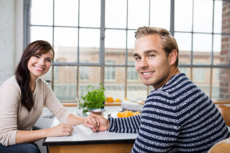 turning table: Happy couple holding hands at breakfast as they sit together at the breakfast table in front of a large window turning to smile at the camera