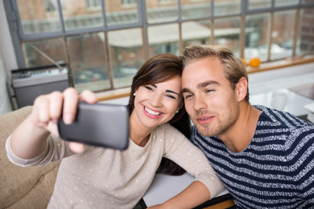 Happy young couple taking a selfie posing with their heads close together smiling at the camera on their mobile phone photo