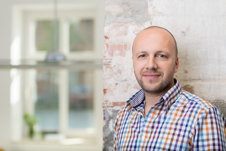 Balding middle-aged man in a checked shirt standing against a painted brick wall looking at the camera with a friendly smile, with copyspace Фото со стока