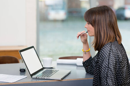 Serious Middle Age Businesswoman Checking Sales at Laptop on Table While Having a Cup of Coffee on Side. Captured Indoor.