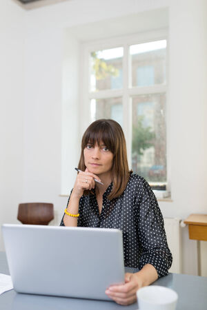 business for the middle: Serious Middle Age Entrepreneur at Gray Gray Office Table Using Laptop for Business While Looking at Camera. Captured Indoor. Stock Photo