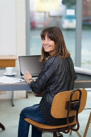 turning table: Young woman working at a table in the office at a laptop computer turning in her chair to smile at the camera Stock Photo