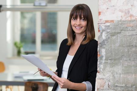 jornada de trabajo: Empresaria atractiva lidiar con el papeleo apoyado contra una pared en la oficina de la celebración de un documento en sus manos sonriendo a la cámara