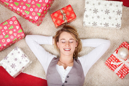 Overhead view of a pretty young woman surrounded with Christmas gifts lying on her back on the carpet with her eyes closed and a smile of contentment