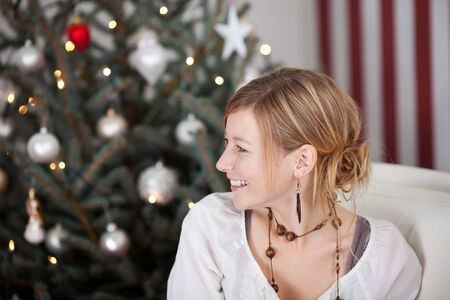 elegant woman looking to a side beside the christmas tree photo