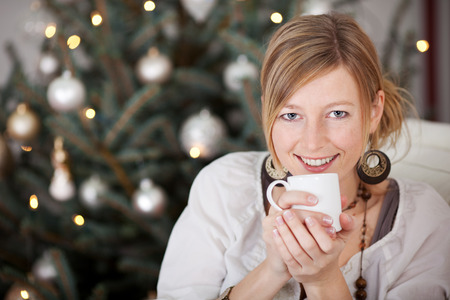 happy blond woman with a cup of coffee beside the christmas tree photo