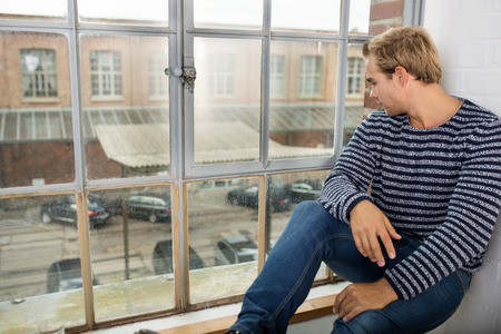 man looking out: Young man sitting on the windowsill in his apartment looking out of a window at the parking lot and urban street below