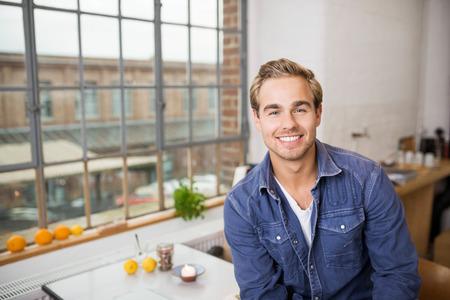 bonhomme blanc: Amical jeune homme avec un beau sourire assis dans sa cuisine dans son appartement urbain en face de la fen�tre en regardant la cam�ra