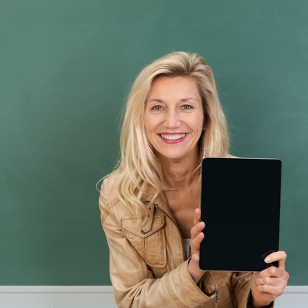 Vivacious stylish middle-aged teacher displaying a blank tablet as she stands in front of the chalkboard photo