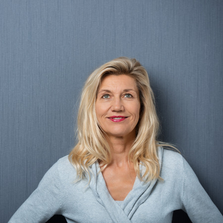 boomer: Close up Smiling Adult Woman with Blond Hair Looking Up on Gray Wall Background.