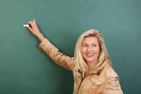 Attractive stylish blond woman teacher writing on a blank blackboard in class turning to watch her students photo