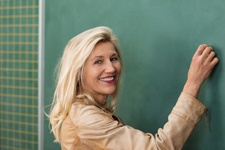 Vivacious attractive blond middle-aged female teacher writing on a class blackboard turning to smile at the camera photo