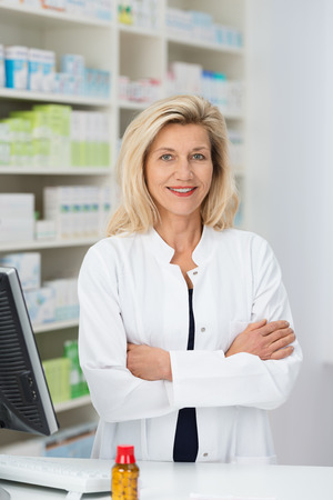 Confident friendly female pharmacist standing with folded arms smiling at the camera behind her desk in the pharmacy