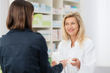 Smiling middle-aged woman pharmacist dispensing a prescription to a female patient as she stands behind the counter in the pharmacy