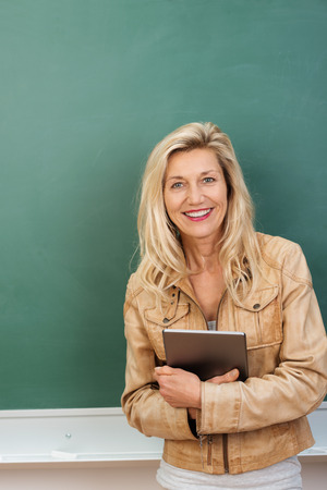 clutching: Smiling attractive middle-aged teacher wearing a fashionable leather jacket standing in front of a blackboard clutching a tablet to her stomach