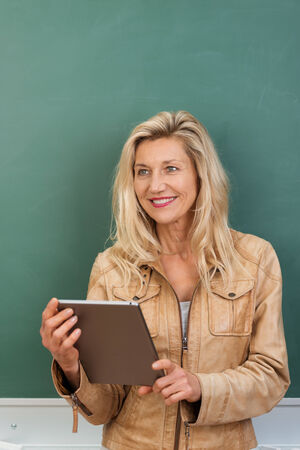 boomer: Thoughtful teacher standing holding a tablet computer in her hands watching something to the side of the frame