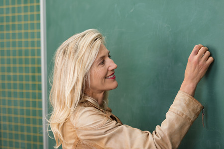 Close up side view of an attractive middle-aged blond teacher in a trendy jacket smiling and writing on the blank chalkboard photo