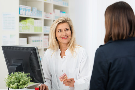 pharmacy: Pharmacist helping a customer in the pharmacy smiling as she takes payment for medication from a woman with her back to the camera