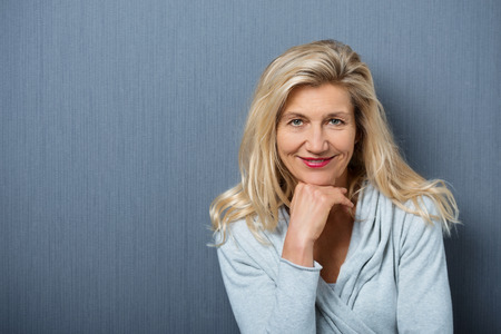 boomer: Close up Attractive Mature Woman, with Blond Hair, Posing with Hand on the Chin. Captured with Gray Wall Background. Stock Photo