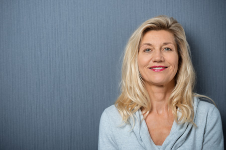 boomer: Close up Happy Adult Blond Woman Leaning on Gray Wall Background while Smiling at the Camera.