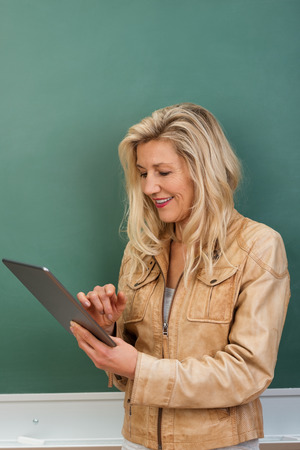 boomer: Attractive blond middle-aged female teacher looking up class work on a tablet computer as she stands in front of the chalkboard