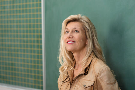 Attractive female teacher or university lecturer standing thinking in front of a blank blackboard looking into the air with a contemplative expression photo