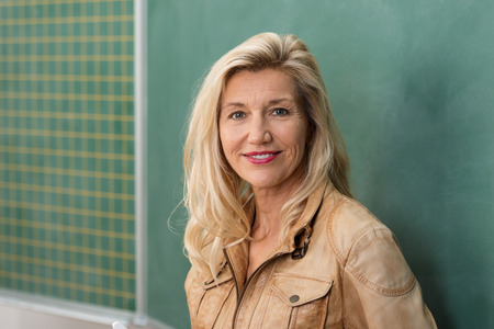 Attractive stylish middle-aged woman teacher standing in front of the class blackboard looking thoughtfully at the camera with a smile