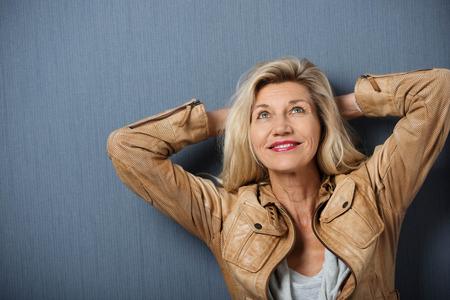 Aantrekkelijke volwassen vrouw denken met haar handen achter haar hoofd leunend op een donkere achtergrond op zoek in de lucht met een glimlach
