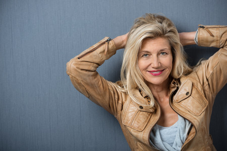 Smiling friendly middle-aged woman standing with her hands clasped behind her head looking at the camera, studio background with copyspace Stock Photo