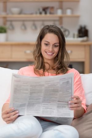 Attractive young woman sitting on a sofa in the living room reading a newspaper and smiling at the news