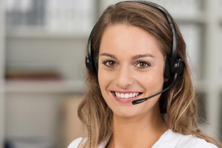 Mujer atractiva joven con una sonrisa que llevaba un auricular para la comunicación en línea como soporte cliente virtual profesional o de servicio al cliente Foto de archivo